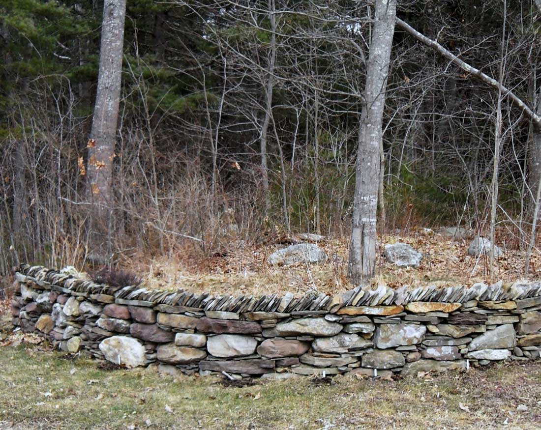 Dry-laid natural stone retaining wall with traditional British-style coping