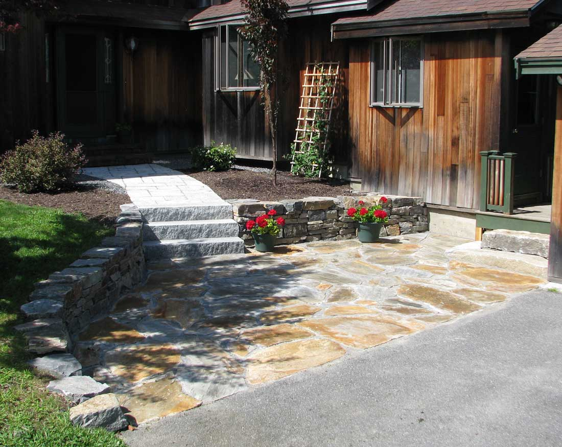 Flagstone patio with natural stone wall and granite steps